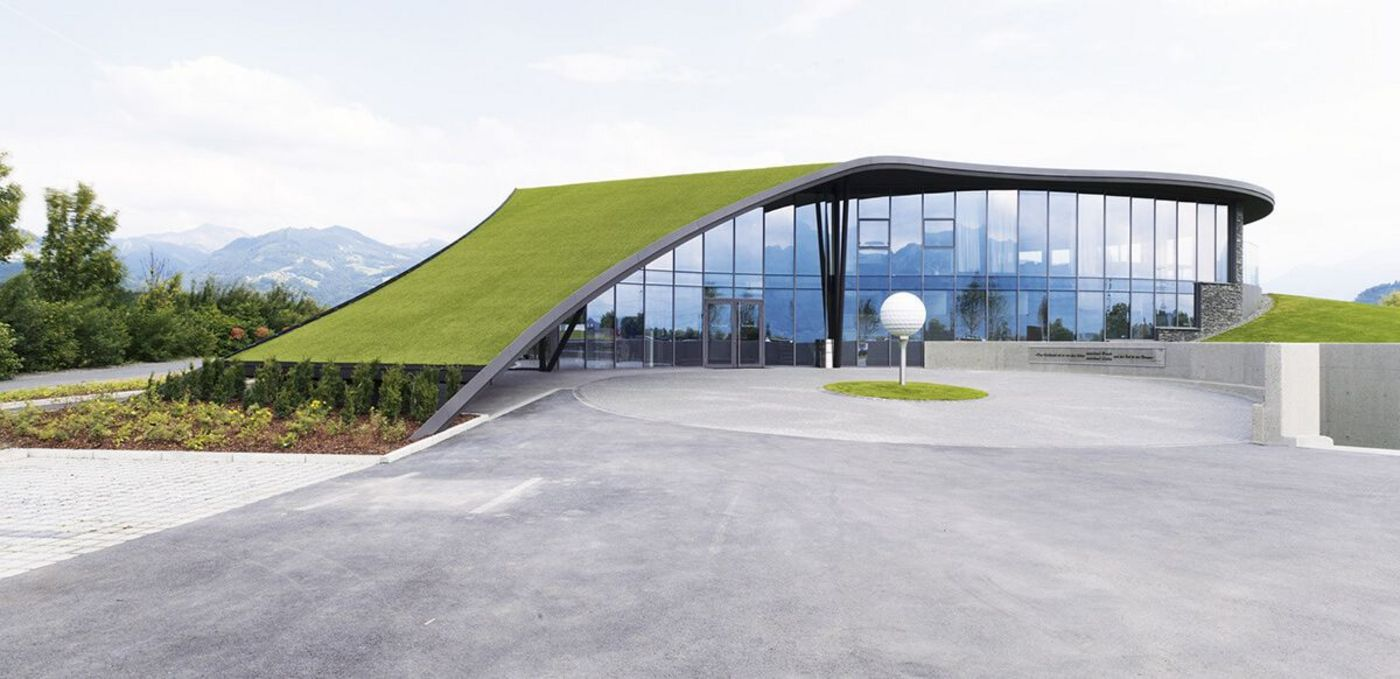 Photo: new clubhouse with panoramic glass façade and roof covered in grass to look like a golfing green; in the middle of the asphalt forecourt an oversized tee with a golf ball