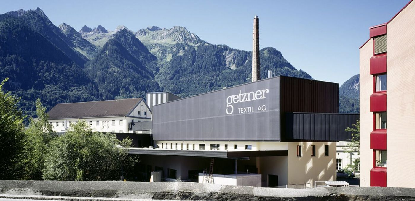 Photo: modern production building belonging to Getzner Textil AG with a connecting bridge leading to the adjacent office wing, behind it other buildings, an old industrial chimney and mountain slopes partly covered in trees